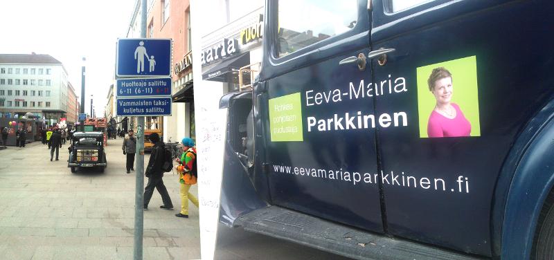 Eeva-Maria Parkkisen kasvot ja keskustan mainokset koristivat autoa.