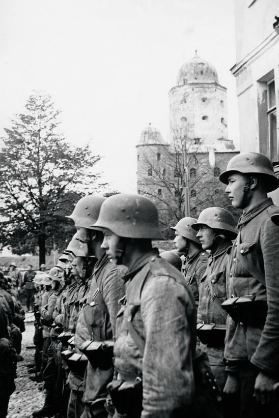 Osa Viipurin vallanneiden joukko-osastojen sotilaita muodosti kunniapataljoonan voitonparaatia varten linnansillan aukiolle. Kuva: SA-kuva.