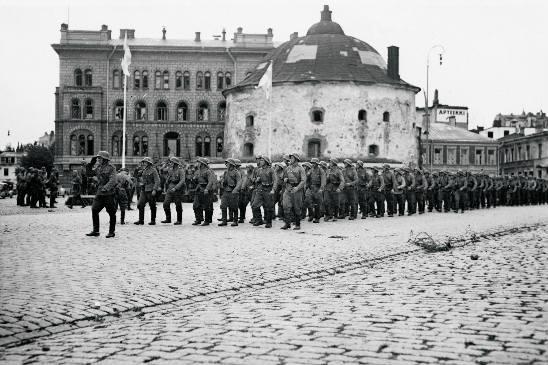 Kunniapataljoona marssi Pyöreän tornin ohi, minkä edustalla kenraaliluutnantti K. L. Oesch otti sen vastaan kunniakorokkeella. Kuva: SA-kuva.
