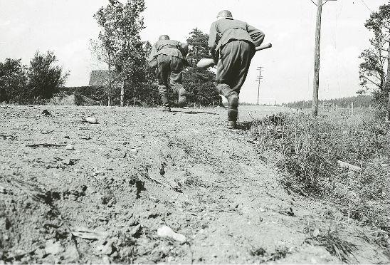 Panssarinyrkkimiehet ylittävät vihollisen tulituksen kohteena olevaa tietä. Kuva: SA-kuva.