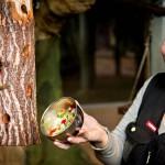 Eläintenhoitaja Merja Helanne tarjoaa marmosetille kesäistä kasvissalaattia.