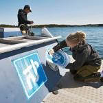 Saana Väänänen liimaa PSS:n tarrakuvaa kelluvaan imutyhjennysasemaan, joita Saaristomerellä on kaikkiaan 12 kappaletta.