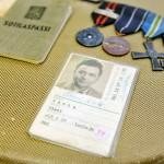Sotasankari Olavi Virta otti ikätovereittensa ohella osaa sekä talvi- että jatkosotaan. Alikersantti Virta aloitti sodankäyntinsä jouluna 1939 Karjalankannaksen Johanneksessa ja taisteli myöhemmin muun muassa Kuolemajärvellä ja Viipurin alueella. Asemasotavaiheessa 1941 Virta sai komennuksen viihdytyskomppaniaan ja ryhtyi kiertämään rintamaa viihdytysjoukkojen mukana. Hän toimi myös rintamaradiossa äänittäjänä ja kuuluttajana. Kuvassa ansiomerkkien ja sotilaspassin lisäksi myös joka kansalaisen viinakortti, alkoholiliikkeen antama virallinen henkilötodistus, jonka käytöstä luovuttiin vuonna 1970.