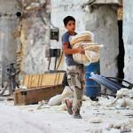 Poika kantaa leipää 2. lokakuuta Al Latamnehin kaupungissa, jossa Venäjän ilmaiskut aiheuttivat tuhoja.