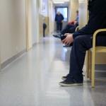 Mies odottaa vuoroaan terveysaseman käytävällä Helsingissä.