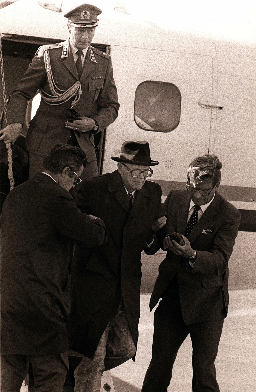 Elokuussa 1981 presidentti Kekkonen palasi viimeiseltä ulkomaanmatkaltaan, joka suuntautui Islantiin. Matkan aikana hänen ajan- ja paikan tajunsa olivat kadoksissa ja hän kärsi harhoista. Turvapäällikkö Teuvo Hirvonen tukee presidenttiä.