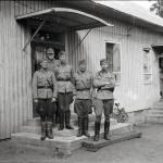 """Sotaoikeuden jäsenet poseeraavat Ylämaan suojeluskuntatalon portailla 24.8.1941. """"8 De:n sotaoikeus on tuominnut 10 desanttia ja vakoojaa."""""""