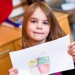 """Aino Lehtisen piirtämä lahjapaketti on kova, painava ja hetken kuluttua avaamisen jälkeen myös herkullinen. """"Äitini kertoi, että hän haluaa joululahjaksi uuden paistinpannun."""" Äidin kokkauksista Ainon on helppo valita suosikkinsa. """"Tykkään kaikkein eniten letuista."""""""