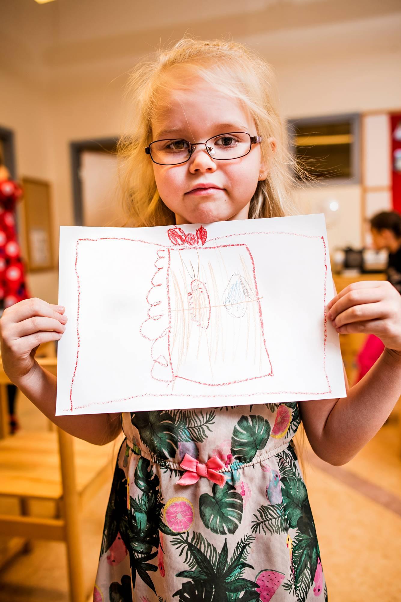 """Rianna Johansson on piirtänyt lahjatoiveensa paperille. Punarusettisessa paketissa on sivistävä sisältö. """"Mun äiti haluaa joululahjaksi koulukirjoja"""", Rianna kertoo."""