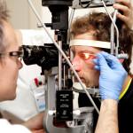 Silmätautien erikoislääkäri Tommi Parkkinen tutkii laserilla Toni Helmisen silmää.