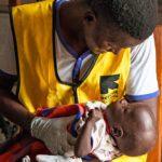 Sairaanhoitaja tutkii kahdeksankuista poikaa, jonka äiti käveli Etelä-Sudanista Kakumaan.