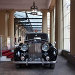 Rolls Royce PhantomIV odottaa palatsin sisäpihalla emäntäänsä. Auto oli ensimmäinen laatuaan ja valmistui mittatilaustyönä vuonna 1950 häälahjaksi 1947 avioituneelle prinsessa Elisabetille.