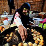 Nainen valmistaa öljyssä perinteisiä dubailaisia herkkuja.