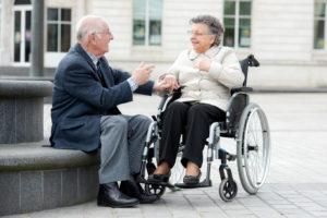 Vanha mies ja pyörätuolissa istuvat nainen.