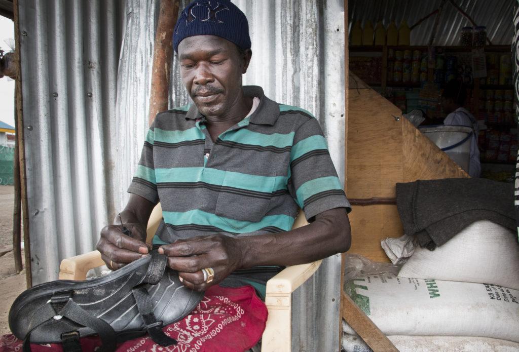 Sudanin sisällissotaa paennut Hussein al Awal korjaa työkseen jalkineita. Työllistymiseen Kakuman pakolaisleirillä on niukasti mahdollisuuksia. Käteisen puute saa monet myymään YK:n jakamia ruoka-avustuksia polkuhintaan.