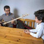 Isä yllättää Kamiran-poikansa soittamalla kurdien tanbura-instrumenttia.