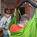 Apuvälineet helpottavat paitsi asiakkaiden arkea myös hoitajien työtä. Mari siirtää Reinon sänkyyn nostolaitteella.
