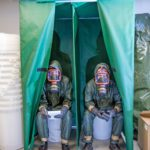 Kansanedustaja Juho Eerola ja toimittaja koeistuvat suojan kuivakäymälät täydet suojavarustukset yllään.