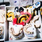 Hammaslaboratoriotyö vaatii useita välivaiheita. Laboratorion pöydällä on hammasjäljennöksiä, hampaiden kipsimalleja ja purentaindeksivahoja.