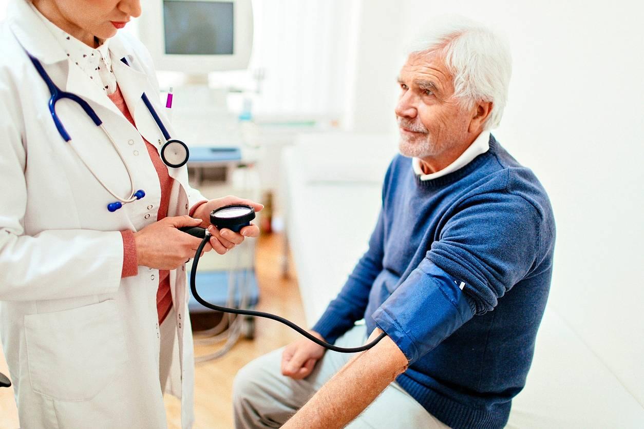 Lääkäri mittaa verenpaineen mieheltä.