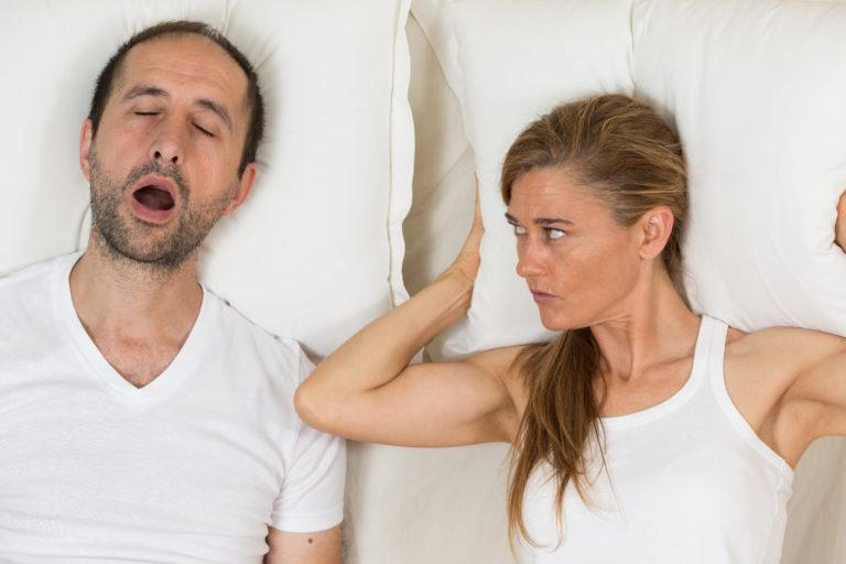 Nainen tarkkailee, kun mies nukkuu levottomasti.