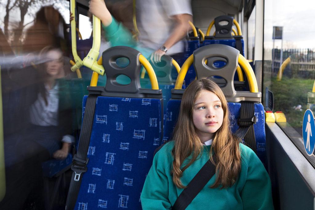 Tyttö bussissa käyttää turvavyötä.