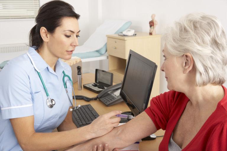 Sairaanhoitaja rokottaa naista.