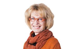 Kirjailija Kaari Utrio hymyilee lähikuvassa.