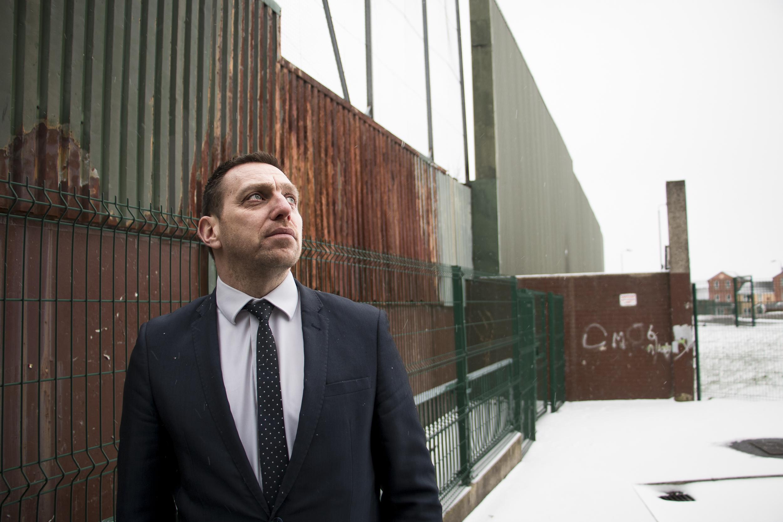 Asianajaja Padraig Ó Muirigh esittelee Belfastin katolilaisten ja protestanttien asuinalueita erottavaa turva-aitaa.