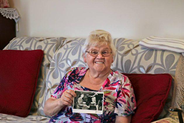 Aila Eskelinen kädesssään mustavalkoinen valokuva laivamatkalta, kun Aila perheineen muutti Australiaan syksyllä 1964. Aila kuvassa oikealla.