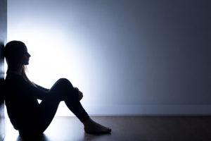 Kuvituskuva: Masentunut nuori istuu pimeässä huoneessa.