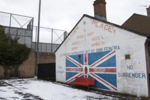 Cluan Placen lähiötä ympäröi aita, joka on korkeampi kuin sen suojaamat talot. Graffiti muistuttaa vuodesta 2002, jolloin viittä lähiön asukasta ammuttiin.