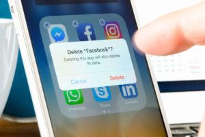 Kuvituskuva: Älypuhelin, jonka köyttäjä on poistamassa Facebook-sovellusta.
