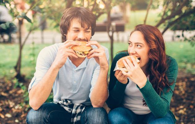 Pariskunta syö hampurilaista