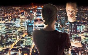 Nainen katsoo ikkunasta kaupunkimaisemaa