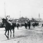 Ylipäällikkö Mannerheim ratsastaa esikuntaryhmänsä kärjessä sisällissodan voitonparaatissa. Taaempana tulevat paraatin pääjoukot. Taustalla näkyy Kansallismuseon torni.