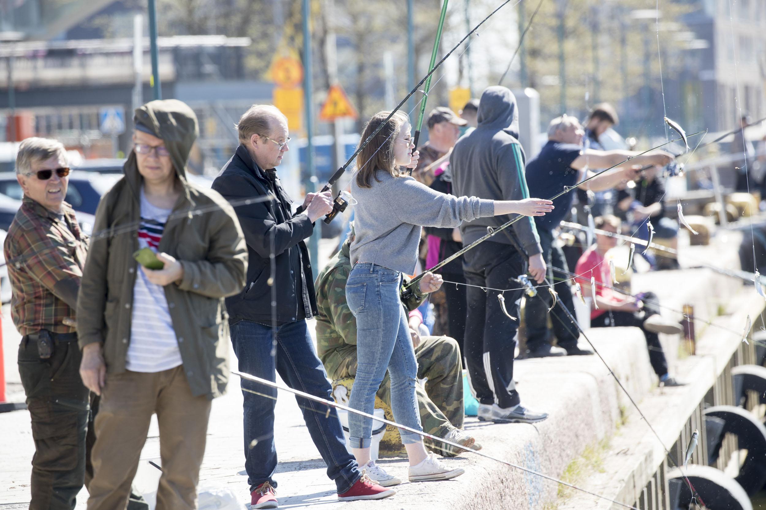 Kaapelitehtaan laituri Lauttasaaren sillan vieressä on suosittu kalastuspaikka Helsingissä. Siellä käyvät myös Markku (kolmas vas.) ja Linda Liukkonen. Kuva Pekka Nieminen / Otavamedia