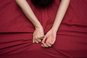 Kuvituskuva: Nainen puristaa kädellään lakanaa.
