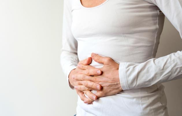 Nainen pitelee kipeää vatsaa
