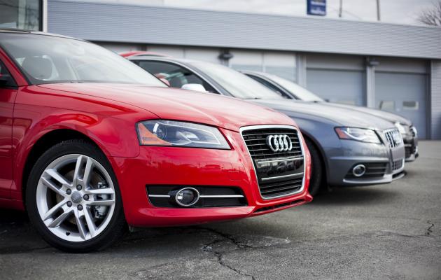 Punainen ja harmaa Audi rivissä parkkipaikalla.