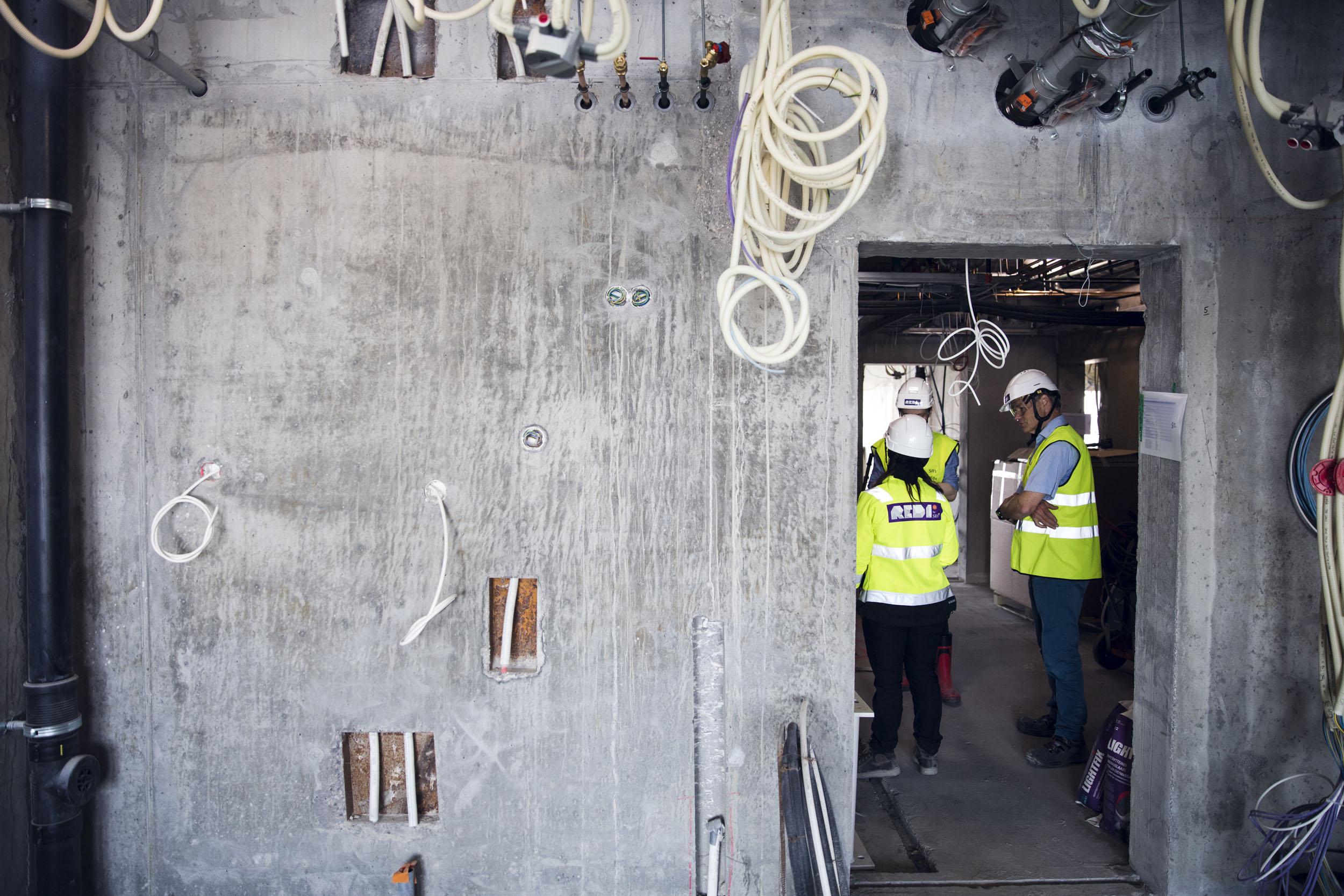 Sähköjohtoja tursuavat betonihuoneistot kaipaavat vielä paljon viimeistelyä, ennen kuin asukkaat pääsevät muuttamaan niihin keväällä 2019.