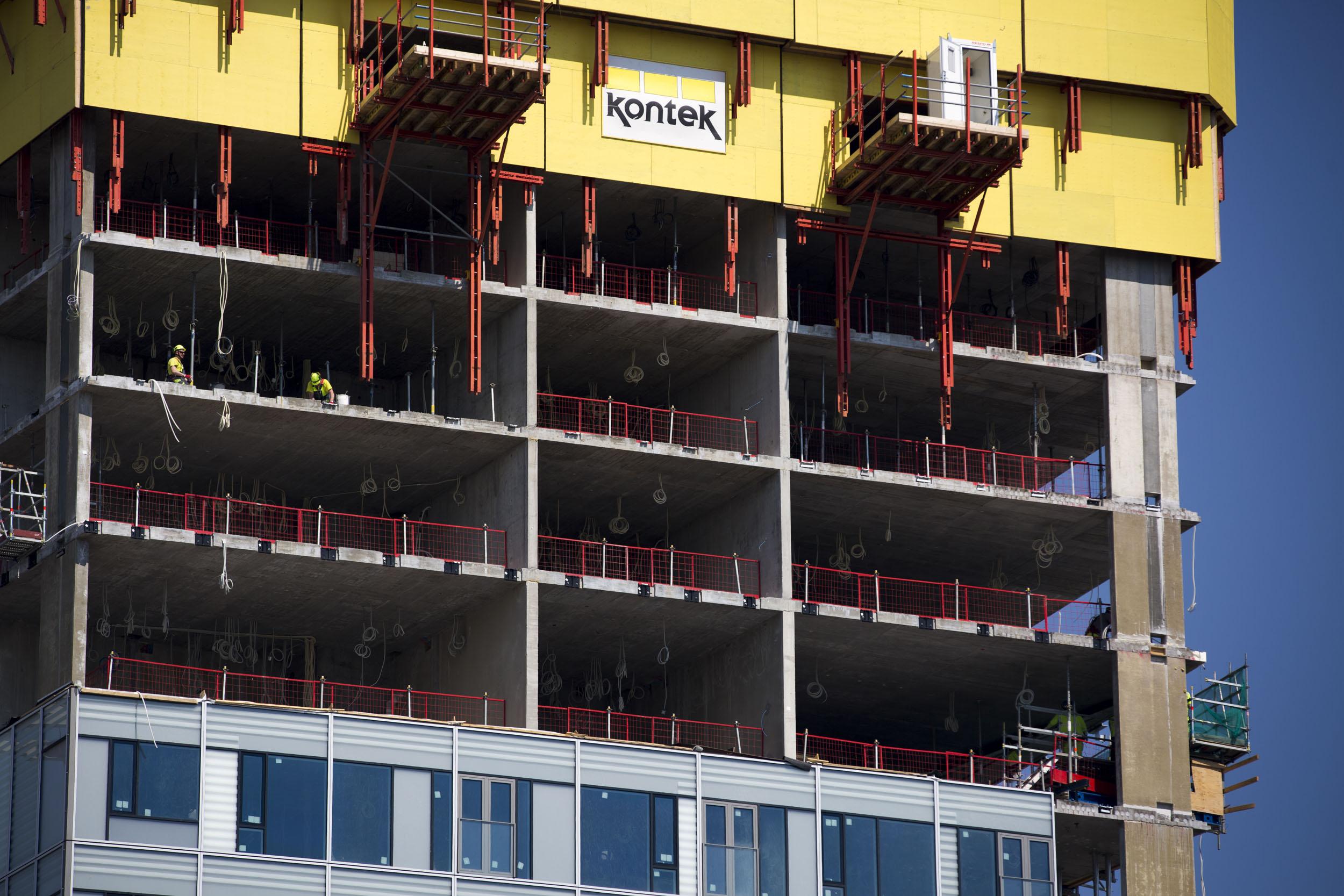 Punaisten palkkien varassa lepää kiipeävä muotti, jonka avulla työntekijät valavat betonista Majakan kantavat seinät ja hissikuilut. Kun yksi kerros on valmis, muotti nostetaan seuraavaan. Julkisivu kiinnitetään rungosta erilleen.
