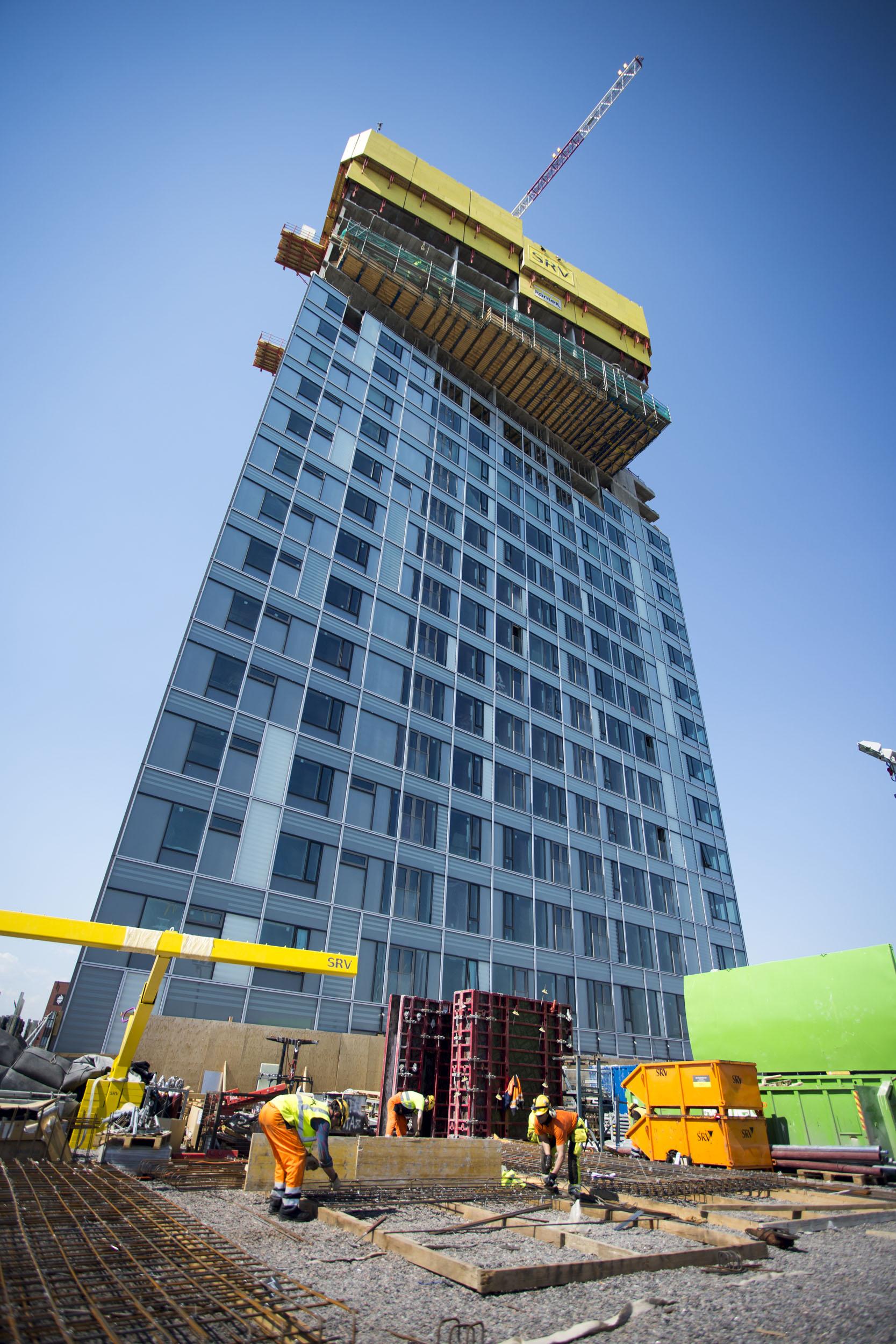 Alhaalla 5. kerroksen kohdalla työntekijät rakentavat julkista puistokantta ja yksityisiä pihoja. Ensimmäiset asunnot sijaitsevat 6. kerroksessa.