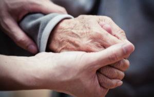 Naisen käsi pitelee vanhuksen kättä.