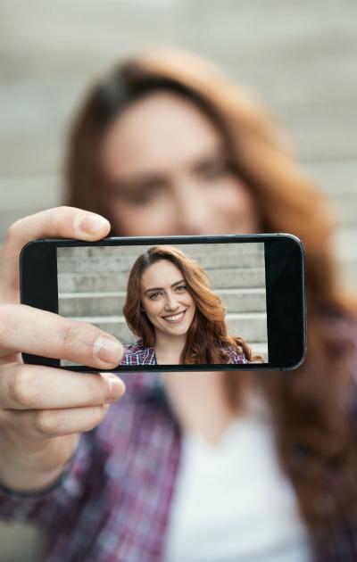 Punatukkainen nainen ottaa selfien.