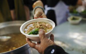Avustustyöntekijä ojentaa ruokaa vähätuloisille.