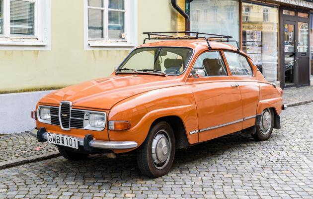 Oranssi vanha Saab kadunvarressa.