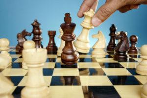 Mies pelaa shakkia.