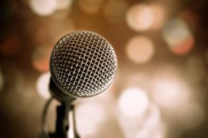 Kuvituskuva: Mikrofoni etualalla, yleisöä taustalla.