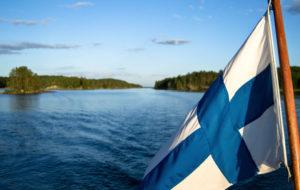 Suomen lippu liehuu idyllisessä järvimaisemassa.
